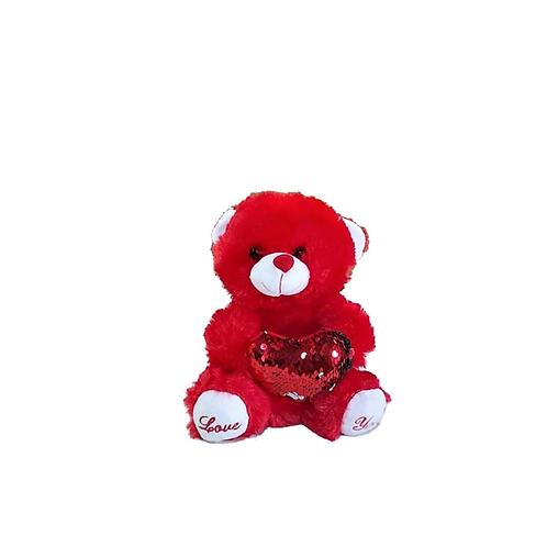 דובון אדום קטן עם לב אדום בוהק בכפותיו