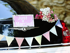 רכב מקושט עם שלט חתונה ודגלי גרלנד