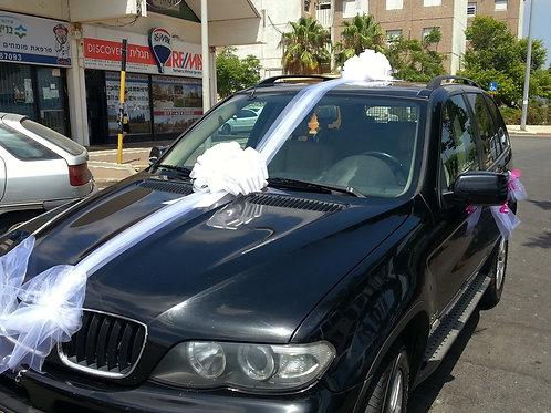 ג'יפ ב.מ.וו מקושט לחתונה בחניה ליד חנות פרחים