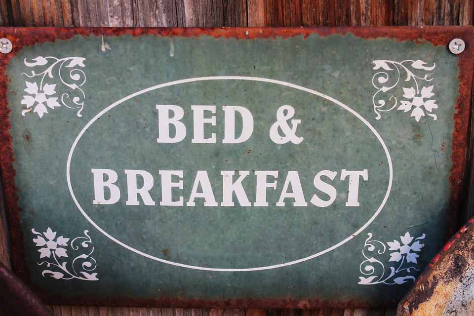 Old green rustic sign that says Bed & Breakfast