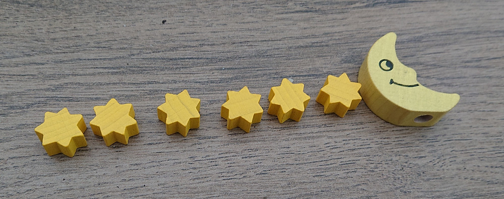 6 star-shaped wooden token and one moon-shaped wooden token arranged in a row.
