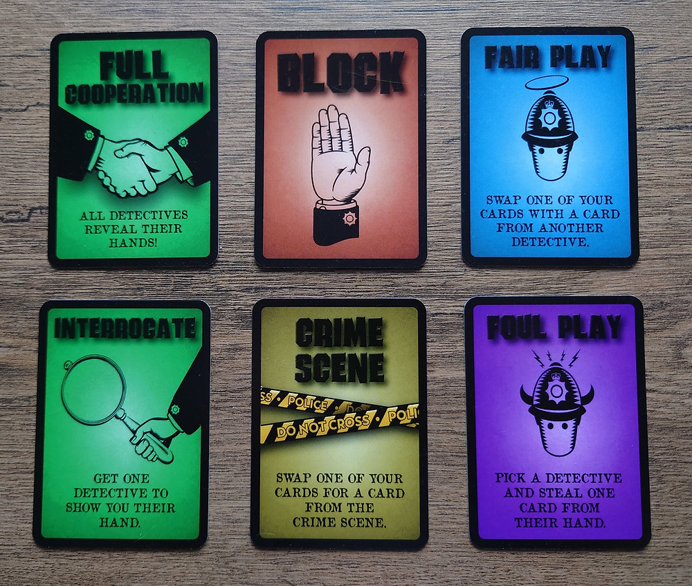 """Six cards arranged into two rows. The cards show the six different actions that can be taken in the game. The two cards on the left have green backgrounds and show the two actions that cause players' hands to be revealed. The top middle card has a dark orange background and shows the block action. The middle bottom card has a yellow background with crime scene tape and shows the """"crime scene"""" action. The top right card has a blue background and shows the card swap action. The bottom right card has a dark purple background and shows the card stealing aciton."""
