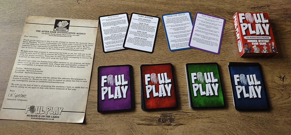 An overview of the components of Foul Play. Four equal size stacks of playing cards arranged into four piles, each with a different coloured card back. Four cards arranged above the four piles, showing the rules of the game and set-up instructions. One card-sized box with Foul Play branding. One A5 sheet designed to look like an aged document which details the game narrative and company contact info.