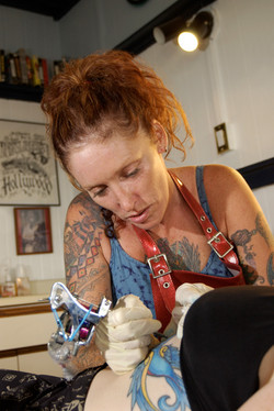 A tattoo artist concentrates while giving a tattoo