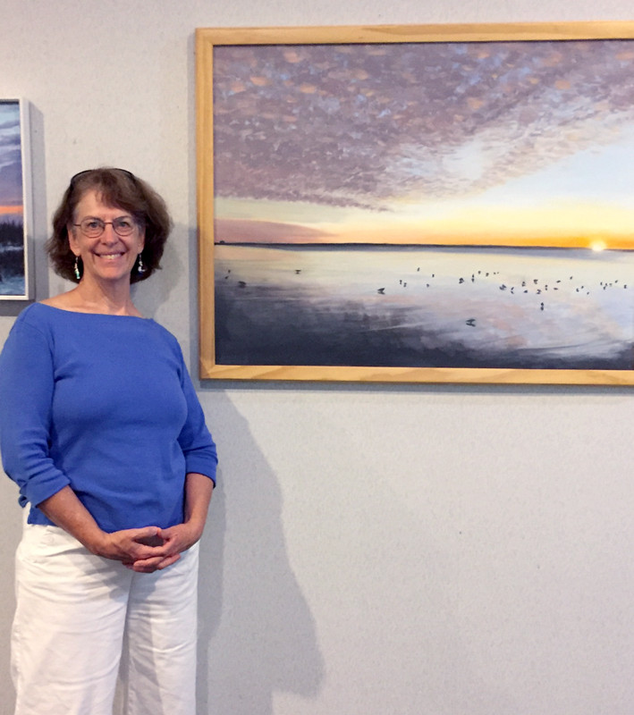 Artist Lora Moran-Collins with one of her paintings.