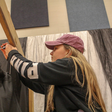 This photo of a student helping take down decorations was taken during prom cleanup. The low angle and leading lines of the wood make this a good shot.
