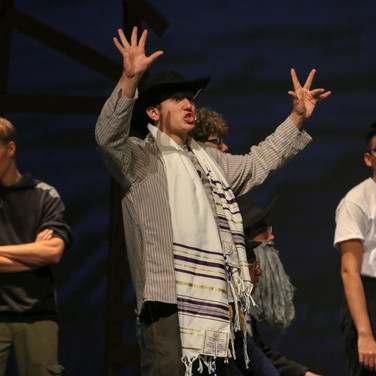 This was shot at a musical practice for Fiddler on the Roof. I like the sharp focus and hand motions from the subject.