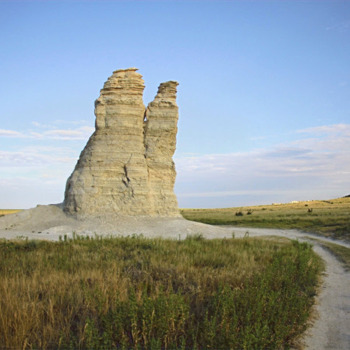 This photo was taken in western Kansas of Castle Rock. I incorporated the road into the photo to add leading lines to the main subject.