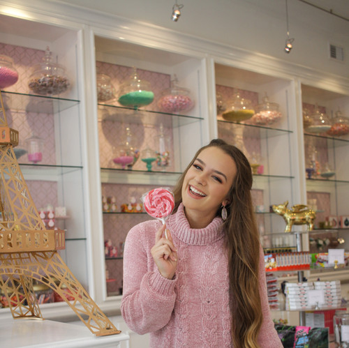 I took this photo in a candy shop and like how I was able to use the candy as a fun prompt. The colorful backdrop and dress also adds to the photo.