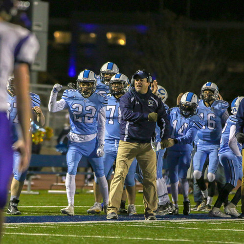 I shot this photo at a playoff football game this season. The coach in front paired with the excited team makes for a great shot.