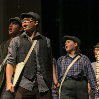 This photo was taken during a school production of Newsies. I like how the formation of the students helps to draw attention to the student in front and the serious expression.