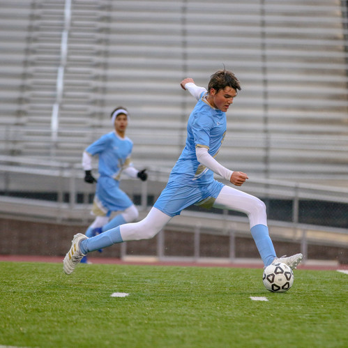 I like the sharp focus and emotion of this soccer photo of a player going to kick the ball upfield.
