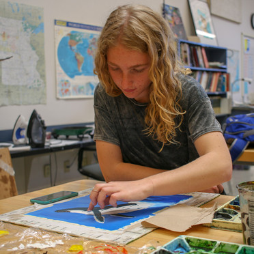 I chose to include this photo of a student fingerpainting a whale as I like the composition of the shot and the busy room that adds to the background.