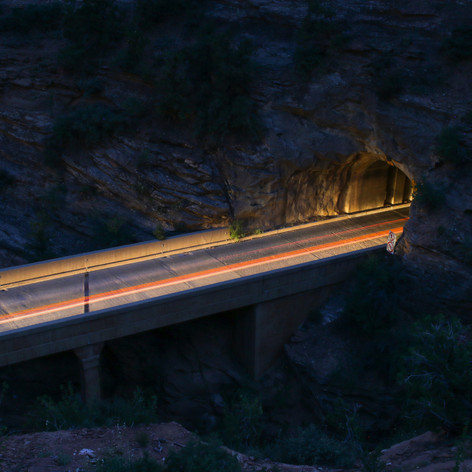 This photo was taken on a trail above a tunnel at night. I used a slow shutter speed to be able to capture the light trails of passing cars.