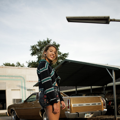 I shot this photo of a friend for fun by an auto shop. I liked the vintage look of the background paired with her outfit and the angle I took the photo from.