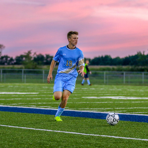 I like the pink colors of the sunset against the bright field in this photo of a soccer player preparing to kick the ball.