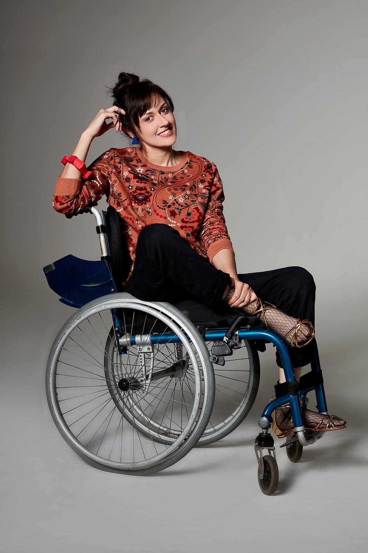 #pracegover: Michele esta sentada de lado em sua cadeira de rodas, usando calça de moletom preta, blusa de moletom caramelo com estampa floral. Nos pés usa meia de tule preta, com sandália dourada.