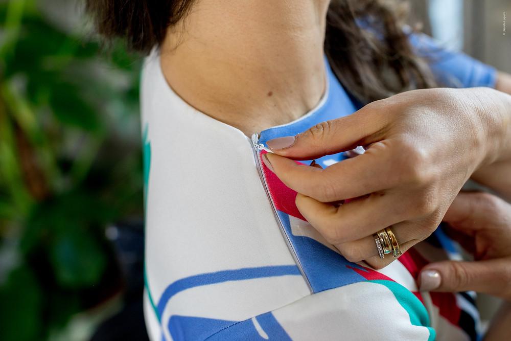 a foto enquadra o a axila da modelo, que mostra um vestido, cujo zíper na lateral do corpo, facilita o vestir para quem tem mobilidade reduzida.