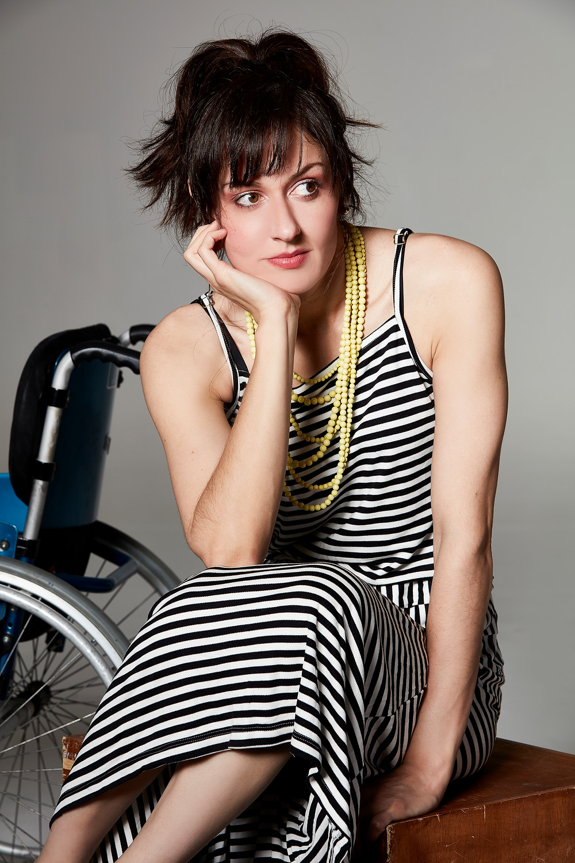 #pracegover: Michele esta sentada sob um tablado de maderia, usando um vestido branco de listras pretas e um colar de 6 voltas amarelo
