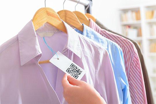 foto de camisas com diferentes cores e padronagens penduradas pelo cabide, com etiquetas em QR Code