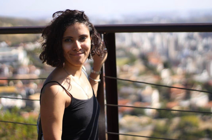 foto de Mariana em plano médio com fundo desfocado do alto da cidade. Ela se apoia em uma grade e sorri de boca fechada. Ela usa uma regata preta, um relógio e uma pulseira no braço a direita na foto e um brinco de argola.