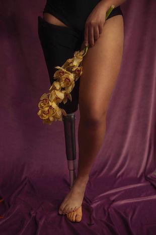Vista da cintura para baixo, uma mulher branca, de calcinha preta, a perna direita tem uma prótese de metal na altura do joelho, a perna esquerda está meio dobrada com o pé sobre o pé da prótese. Ela segura um ramo de flor amarela em frente às coxas.