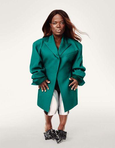 mulher negra com nanismo, magra, com cabelos soltos e liso, usa blazer de alfaiataria verde, calça cigarrete branca e sapatos de bico fino prateado com adorno retangular no peito dos pés.