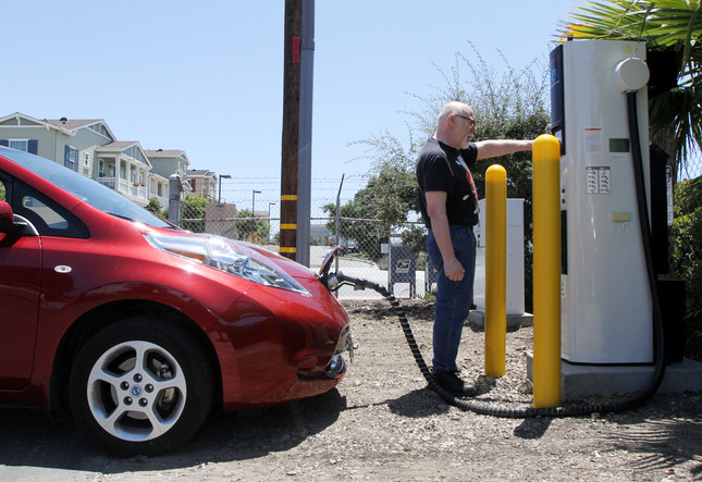 Eric Damron of Tenino, Wash., charges up his Nissan Leaf electric car at Boardwalk Nissan in Redwood City