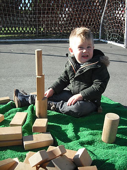 Boy playing outside with wooden bricks