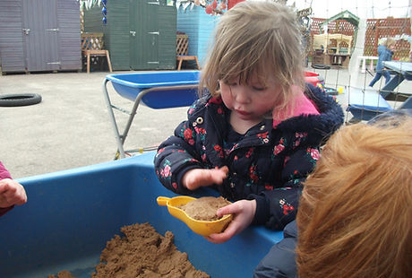 Children playing outside with a sand pit