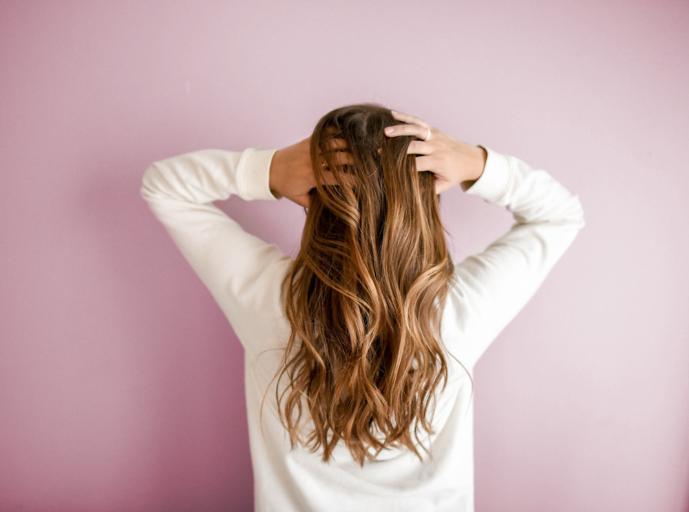 A woman washing her hair with dry shampoo