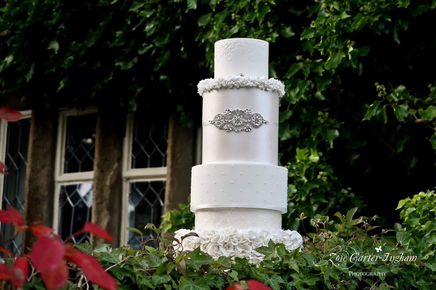 Luxurious all white 5 tier wedding cake with lustre, sparkles, stencilling, ruffles and a bridal bel