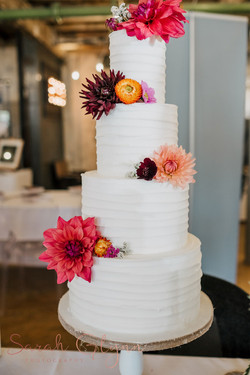 4 tier rustic buttercream wedding cake with fresh dahlia flowers