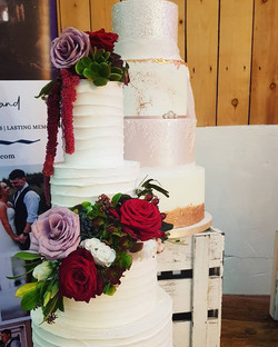 Rustic buttercream wedding cake with fresh flower arrangement