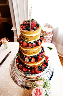 4 tier naked wedding cake decorated with fresh summer fruits