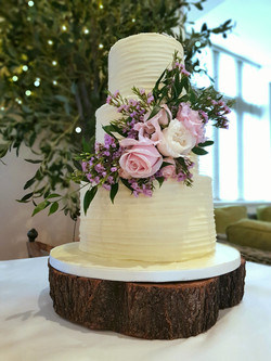 3 tier buttercream wedding cake decorated with fresh flowers