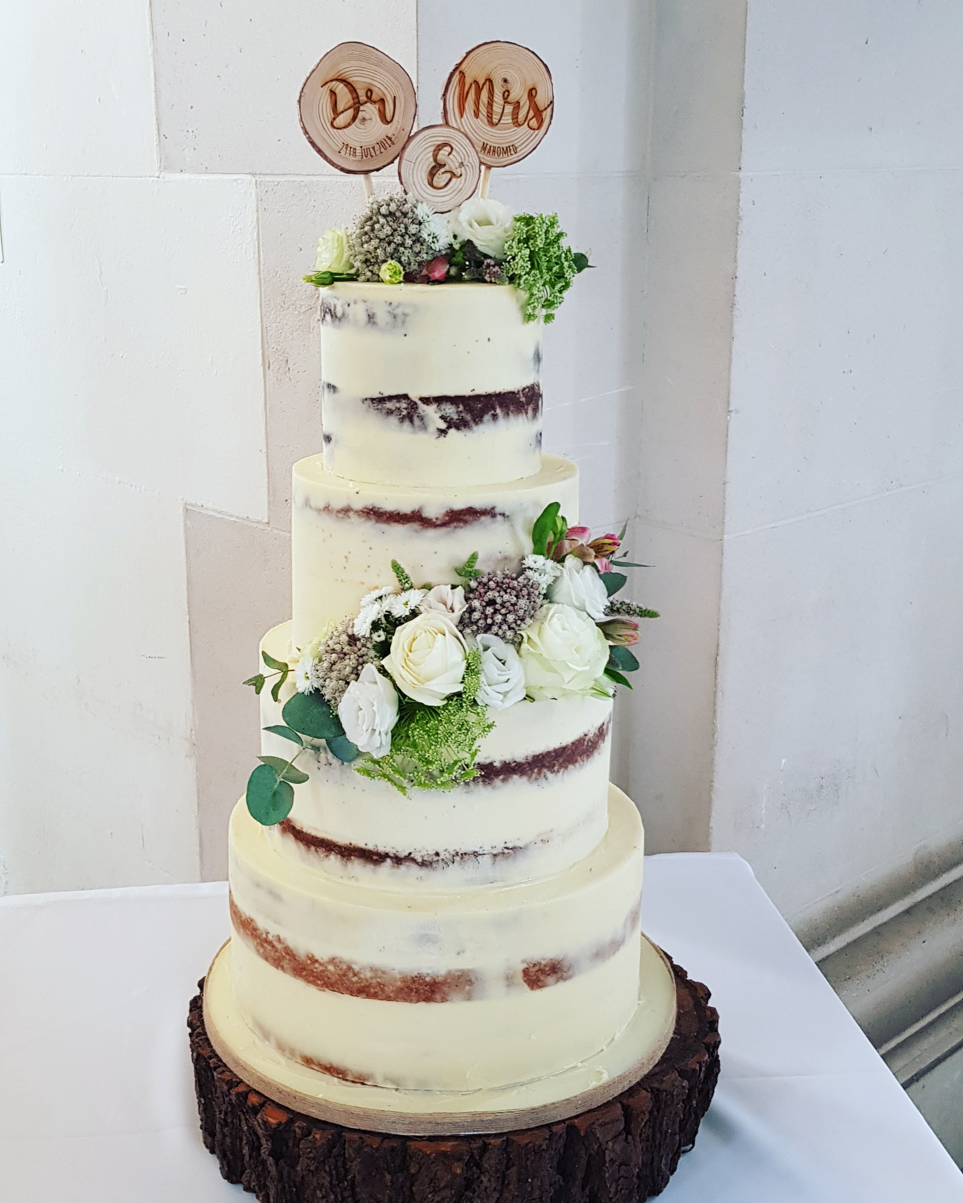 4 tier semi naked wedding cake with fresh flowers