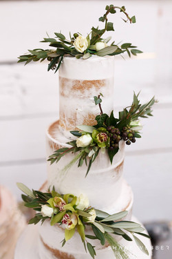Semi naked 3 tier wedding cake with fresh flower arrangements