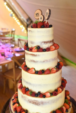 4 tier rustic semi naked wedding cake decorated with fresh summer berries