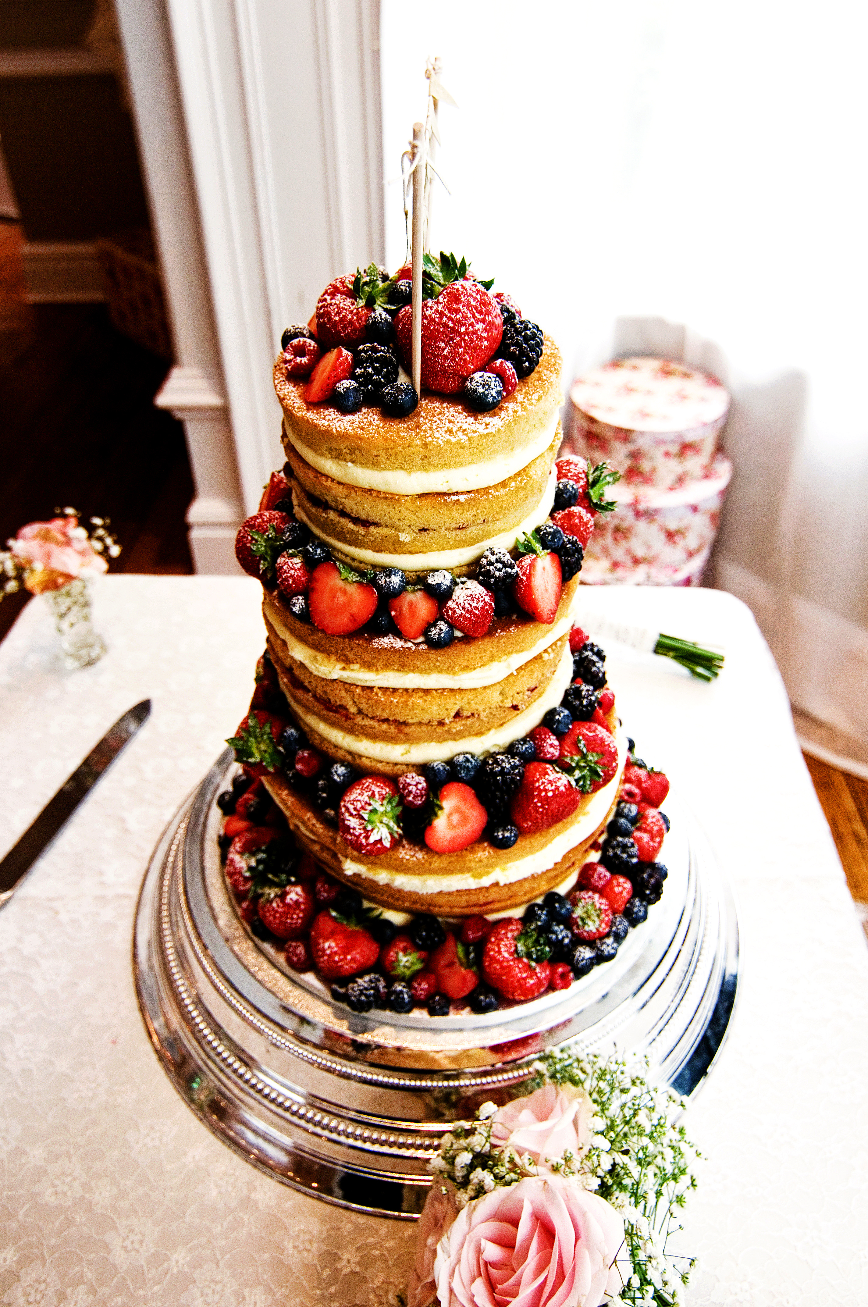 4 tier naked wedding cake with fresh summer berries