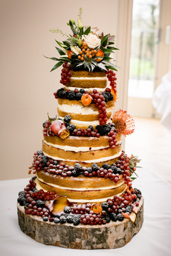 Autumnal naked wedding cake decorated with autumnal flowers and winter berries