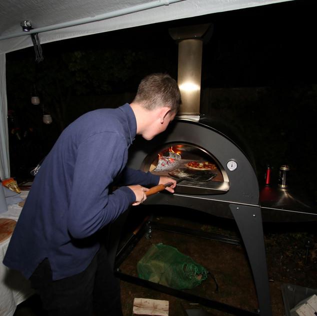 Oli cooking pizza at night.JPG