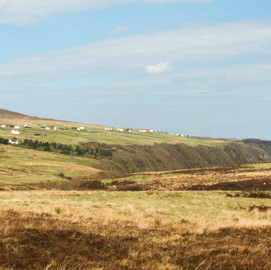 Long distance view of Green Pastures Cottage overlooking the sea