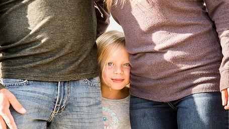 girl's face between her parents slight smile