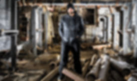a man staring at the camera in an dirty industrial building
