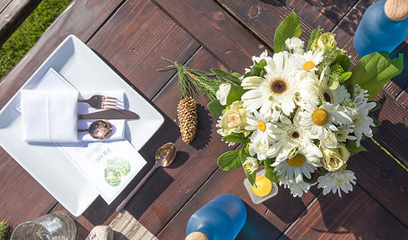 a picnic setting on a wooden bench with flowers
