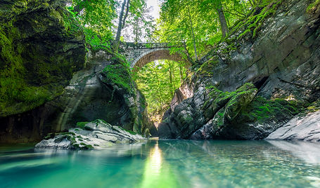 a calm river flowing under a bridge