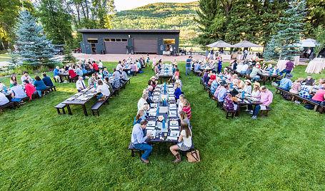 a group of people many picnic tables enjoyinga meal