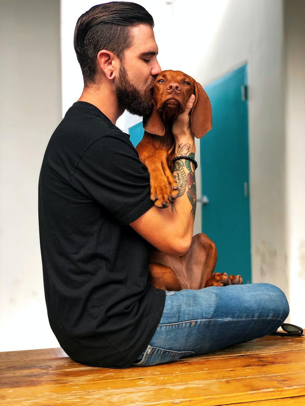 A man in a black t-shirt and jeans embraces his brown hound dog.