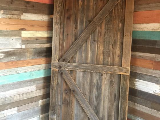 Barn door against colored barnwood wall